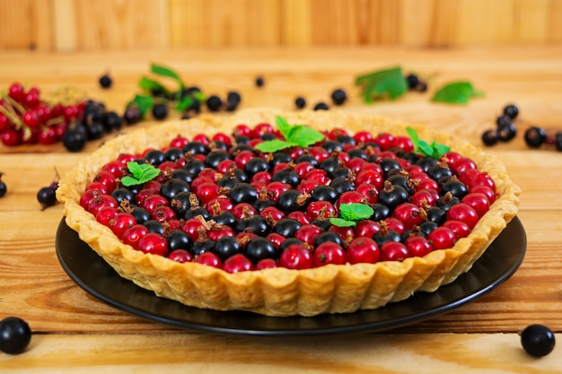 Delicious tart with custard and currant on wooden