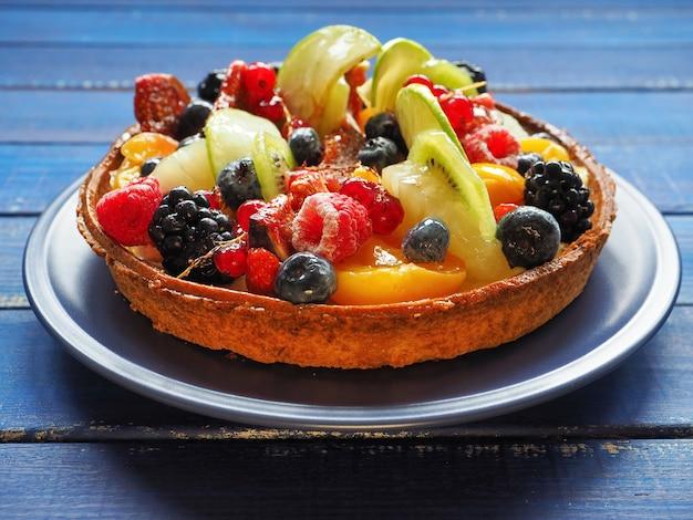 푸른 나무 표면에 이국적인 과일과 열매와 맛있는 타트