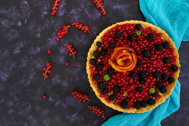 Delicious tart with red currants, peach and blackberries. top view