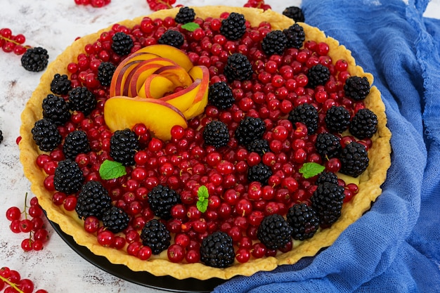 Delicious tart with red currants, peach and blackberries