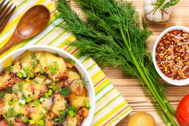 나무 테이블 위에 허브와 야채와 함께 맛있는 tartiflette. 평면도.