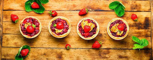 ベリージャムとおいしいタルト。素朴な木製の背景にイチゴとケーキ
