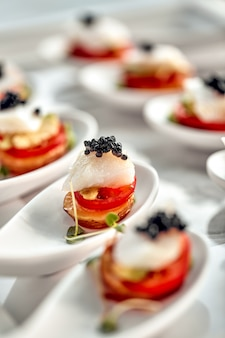 Delicious tartlets with black caviar. concept of food, restaurant, catering, menu.