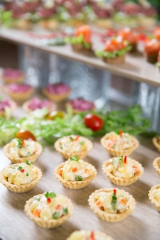 Delicious tartlets with salad on buffet table