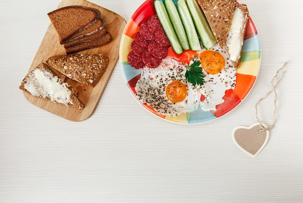 Delicious tasty breakfast on colorful plate with bread on wooden cutting board on white background