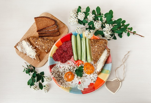 Delicious tasty breakfast on colorful plate with white flowers and bread on white background