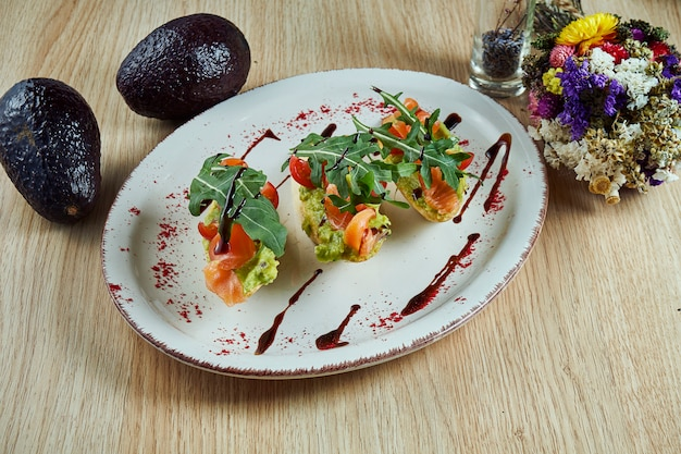 Delicious and tasty bruschetta with salmon, rucola, sauce and avocado. . traditional italian cuisine appetizer. seafood. food photo for menu or recipe