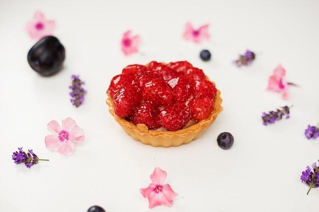 Вкусные вкусные свежие десертные корзины тарталетки из песочного печенья, украшенные малиной среди цветов. концепция выпечки хлебобулочных, сладких блюд. фото крупным планом.