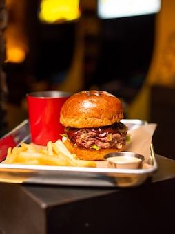 나무 테이블에 쇠고기, 치즈, 베이컨, 소스와 함께 맛있는 맛있는 구운 집에서 만든 햄버거. 감자 튀김과 맥주와 함께 햄버거를 들고 손입니다. 패스트 푸드를 먹는 친구의 그룹