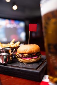 복사 공간이 있는 나무 테이블에 쇠고기, 치즈, 베이컨, 소스를 곁들인 맛있는 구운 홈메이드 버거. 감자 튀김과 맥주와 함께 햄버거를 들고 손입니다. 패스트 푸드를 먹는 친구의 그룹