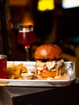 木製のテーブルに牛肉、チーズ、ベーコン、ソースを添えたおいしい自家製ハンバーガーのグリル