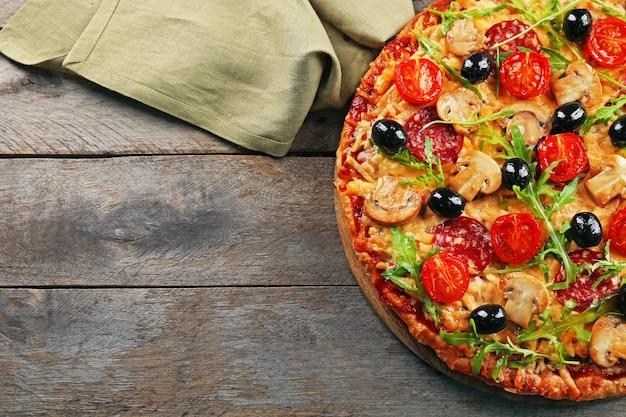 木製のテーブルに材料を使ったおいしいおいしいピザ