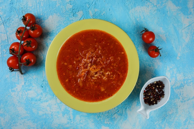 Delicious, tasty tomato soup on the green plate on the blue background. tomatoes and decorative plate with pepper next to the meal.