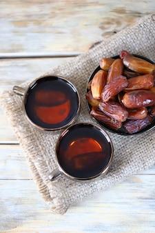 Вкусный чай в чашках и сушеные финики