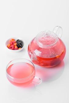 리플렉션 사용 하 여 흰색 배경에 아름 다운 유리 주전자에 딸기와 과일의 맛 있는 차. 모닝 티 파티
