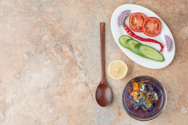 오이, 토마토, 레몬 슬라이스와 하얀 접시에 숟가락으로 맛있는 차