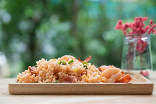 Вкусный тайский жареный рис с креветками на деревянном столе с красивой вазой