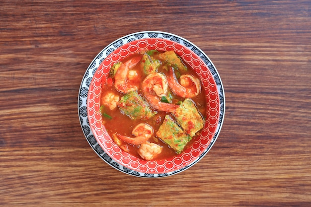 Delicious thai yellow curry with shrimp and fried herb vegetable omelet in bowl
