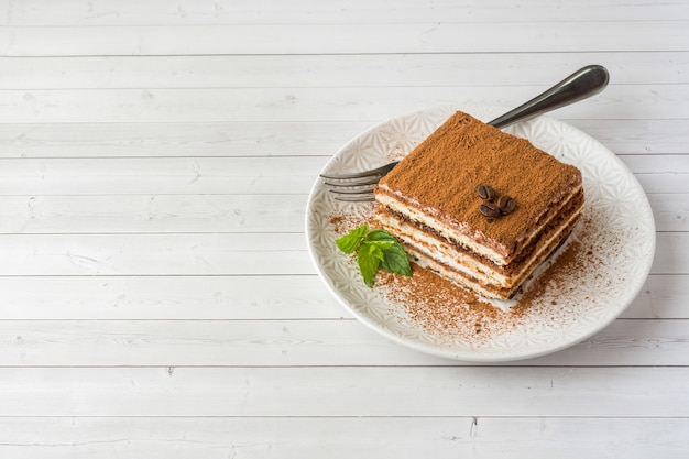 Delicious tiramisu cake with coffee beans and fresh mint on a pl