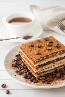 Delicious tiramisu cake with coffee beans on a plate and a cup o