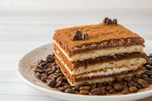 Delicious tiramisu cake with coffee beans on a plate on a light