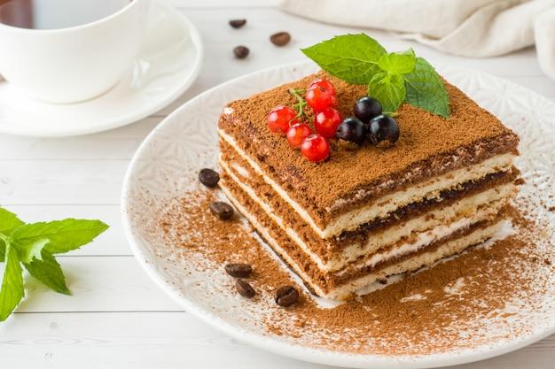 Вкусный торт тирамису со свежими ягодами и мятой на тарелке
