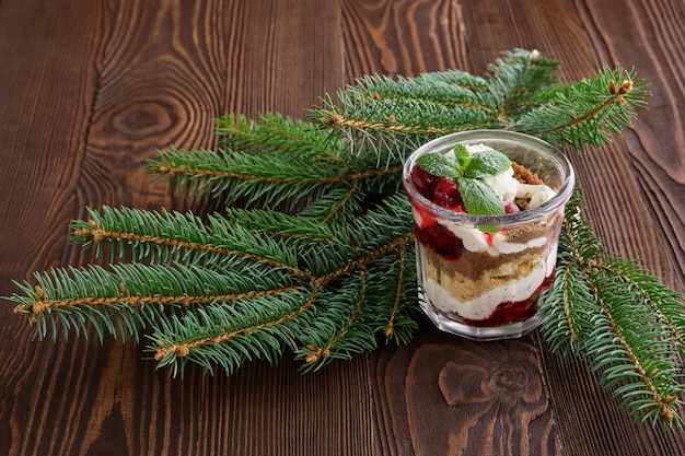 Delicious tiramisu dessert with cherry in rustic pot on dark wooden table