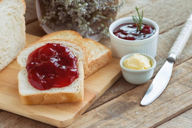 Delicious toast bread served with butter and spread with strawberry jam for breakfast