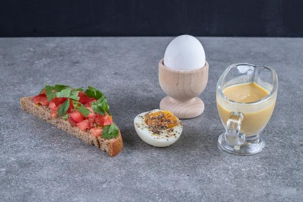 灰色の背景にゆで卵を添えたおいしいトースト。高品質の写真