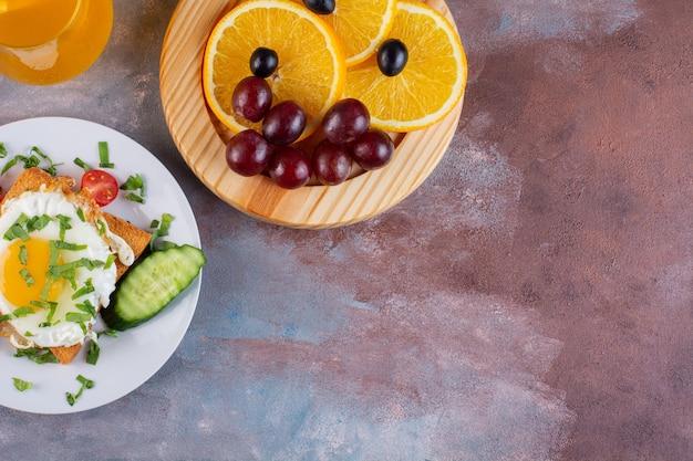 石のテーブルに卵と新鮮な野菜を載せたおいしいトースト。