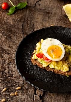 Delizioso toast con crema vegetariana e metà dell'uovo
