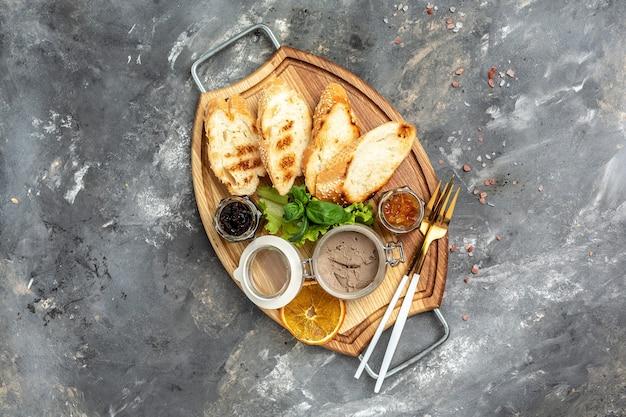 적양파 잼을 곁들인 간 파테 크로스티니, 모듬 이탈리안 애피타이저 브루스케타를 곁들인 맛있는 구운 빵. 배너, 메뉴, 텍스트를 위한 레시피 장소, 상위 뷰.