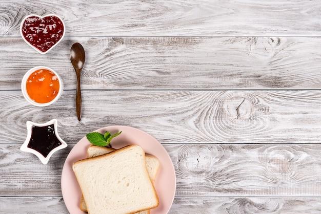 ピンクのプレートに甘いジャムと木の背景に木のスプーンでおいしいトースト。テキスト、バナーのコピースペース。