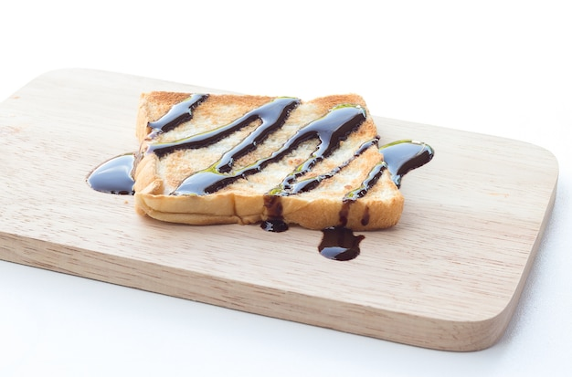Delicious toasts with chocolate syrup on white background