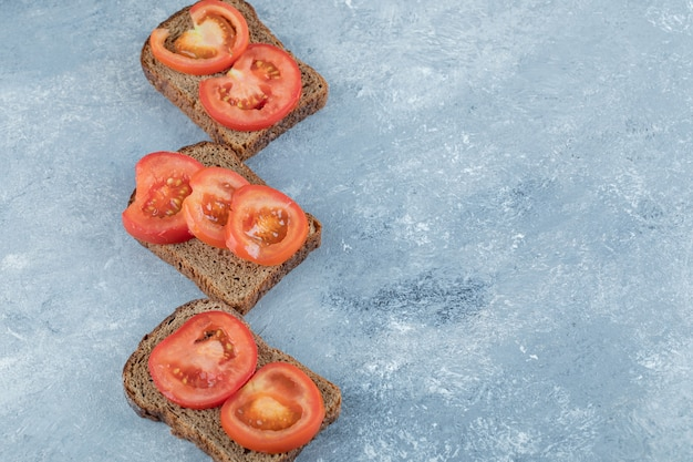 Delicious toasts with slices of tomato on a gray background.