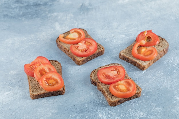 Delicious toasts with slices of tomato on a gray surface.