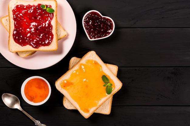 黒の背景にさまざまな甘いジャムとおいしいトースト。テキスト、バナーのコピースペース。
