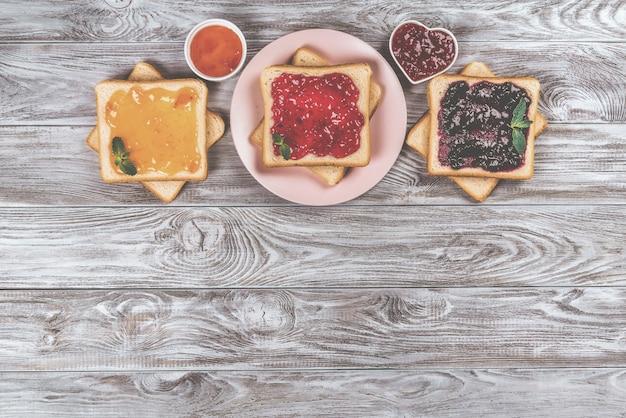 灰色の背景にさまざまな甘いジャムが付いたおいしいトースト。テキスト、バナーのコピースペース。