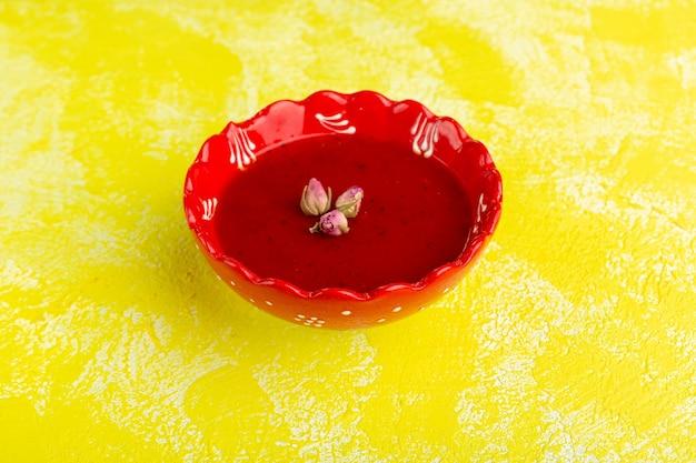 Deliziosa salsa di pomodoro all'interno del piatto rosso su giallo, cibo vegetale di farina di minestra