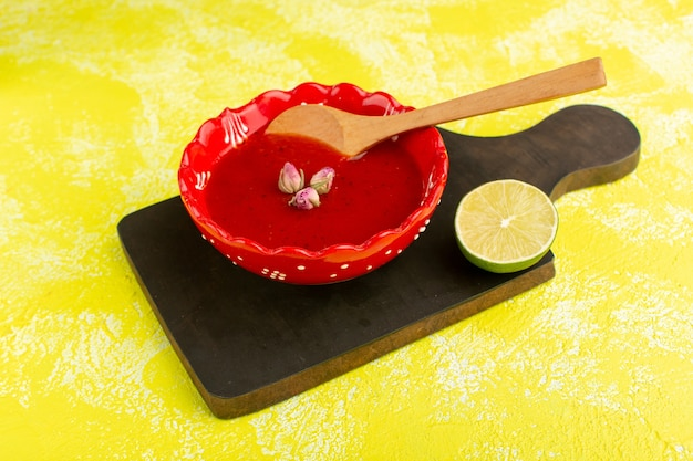 Delicious tomato soup inside red plate with lemon slice on yellow, soup meal dinner vegetable food