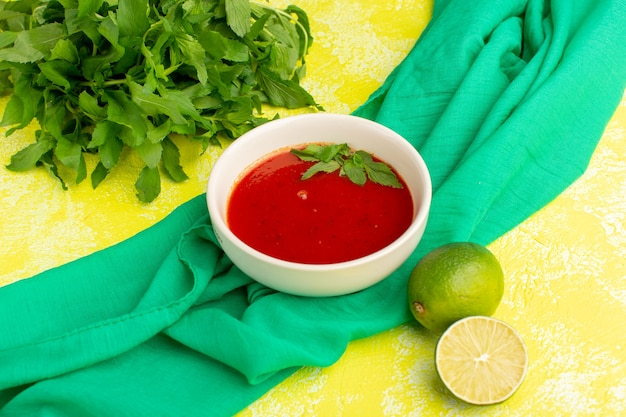 Delicious tomato soup with lemon and greens on the yellow, soup meal dinner vegetable