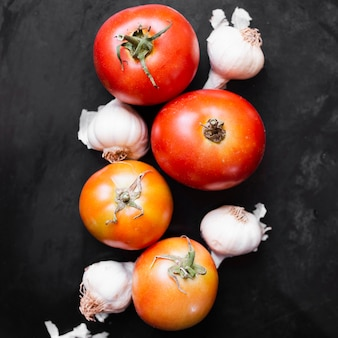Delicious tomatoes and garlic on black background