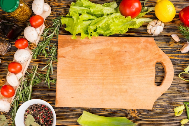 Delicious tomatoes, mushrooms, green leaf lettuce, lemon, garlic and other vegetables surrounding empty cutting board