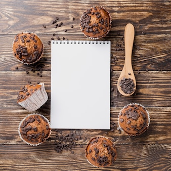 Delicious top view muffins with notepad