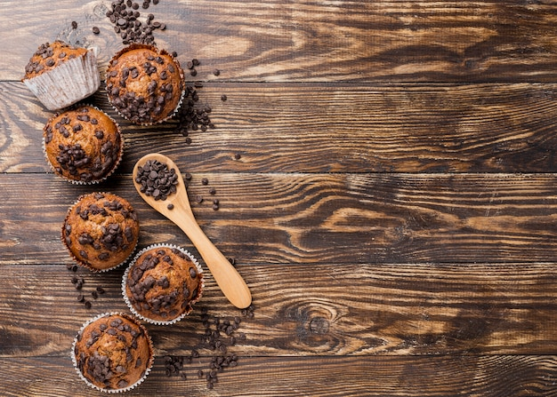 Delicious top view muffins with spoon filled with chocolate chips