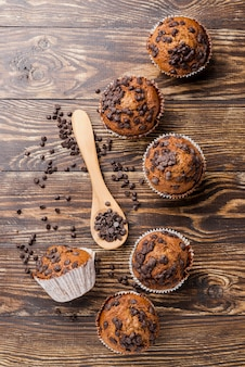 Delicious top view muffins on wooden background