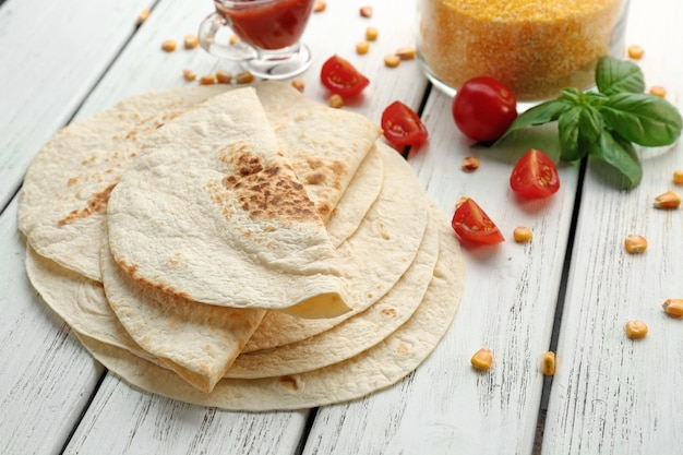 Delicious tortillas on wooden table