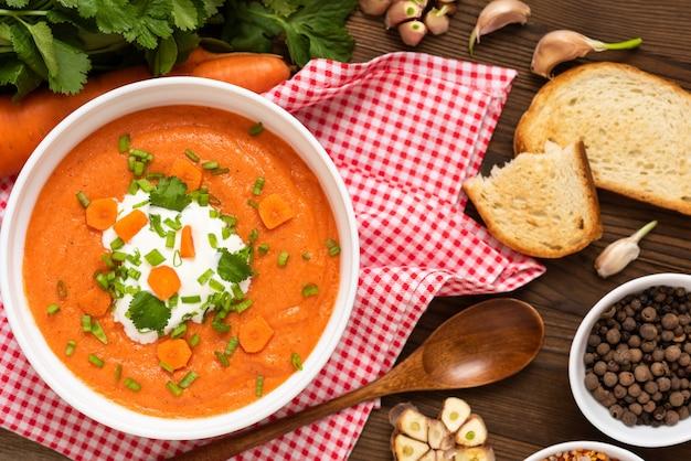Вкусный традиционный морковный суп с зеленью и сметаной на деревянном столе.