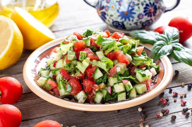 Вкусный традиционный фатуш или хлебный салат с гренками из лаваша, огурцом, помидорами, салатом и зеленью на тарелке на деревянном столе, простой и полезный аутентичный рецепт