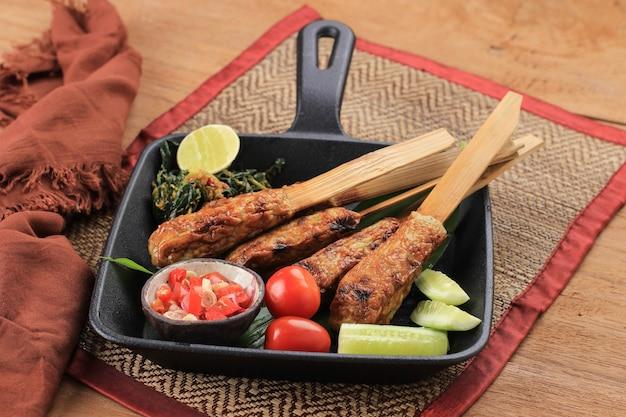 Вкусные традиционные индонезийские балийские кулинарные, сатэ-лилит, сатай из фарша из морепродуктов, приготовленный из тунца и других пряных ингредиентов. в сопровождении самбала матаха, аям бетуту и плесинг кангкунг